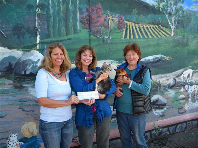 From left, Jane Oatman, president of the Fallbrook Animal Sanctuary (FAS) board of directors, holds a check that was presented by Chris Hawranik of the Bonsall Woman's Club, to Janet LuCore, director, FAS.