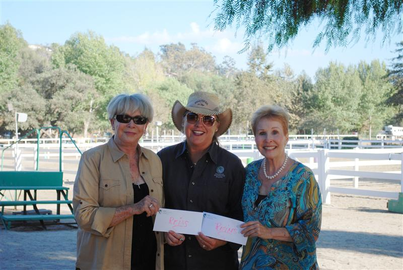REINS executive director Debbie Shinner, center, accepts donations from Bettye Burns, left, and Donna Kovner.