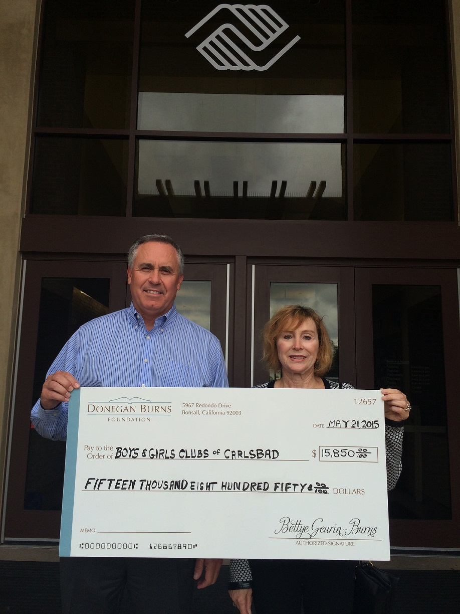 Donegan Burns Foundation Board Member Liz Vasek-Kane presents a check to Carlsbad Boys and Girls Club CEO Brad Holland to cover the cost of repairing the  gym floor at their Carlsbad club.