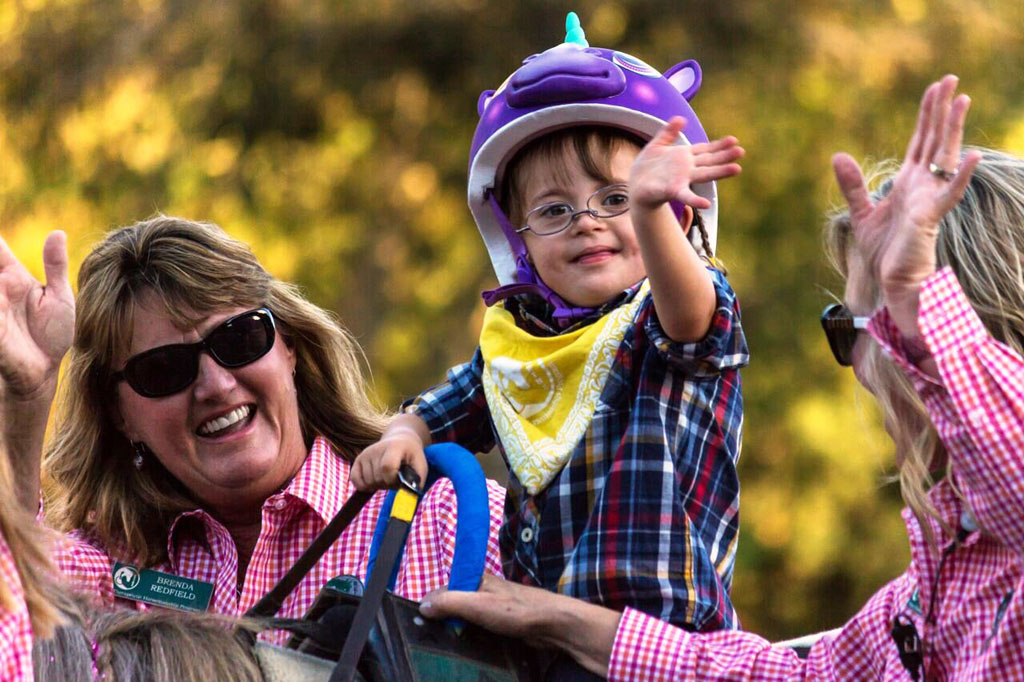 At the REINS annual Country Hoedown fundraiser, a rider happily waves to a crowd of supporters. Connor Kuhn photo